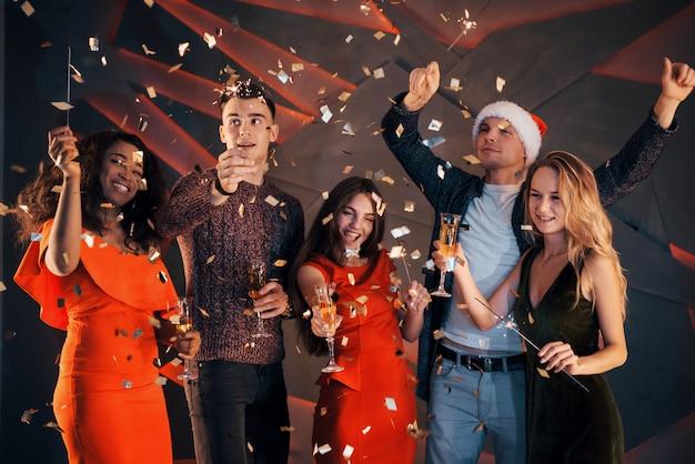 Un grupo de amigos se divierte con hermosos vestidos de gasa con champán y confeti, preparándose para el año nuevo