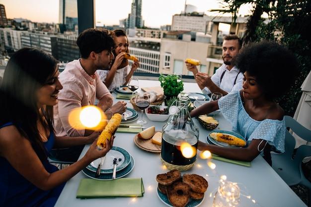 Grupo de amigos divirtiéndose en la azotea de un hermoso ático