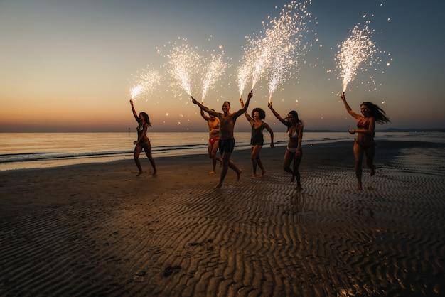 Grupo de amigos divirtiéndose corriendo en la playa con estrellitas