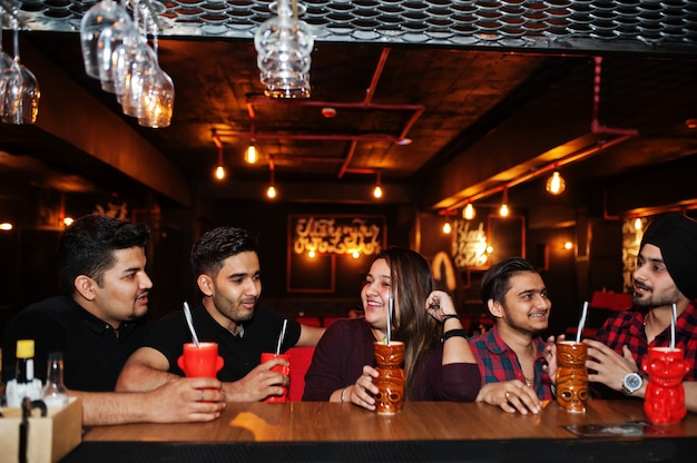 Grupo de amigos divirtiéndose y descansando en el club nocturno, bebiendo cócteles cerca de la barra de bar