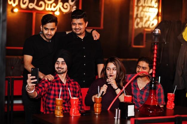 Grupo de amigos divirtiéndose y descansando en un club nocturno, bebiendo cócteles y fumando narguile, mirando teléfonos móviles y haciendo selfie