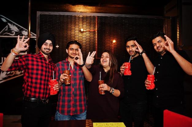 Grupo de amigos divirtiéndose y descansando en el club nocturno, bebiendo cócteles y mostrando los dedos bien juntos