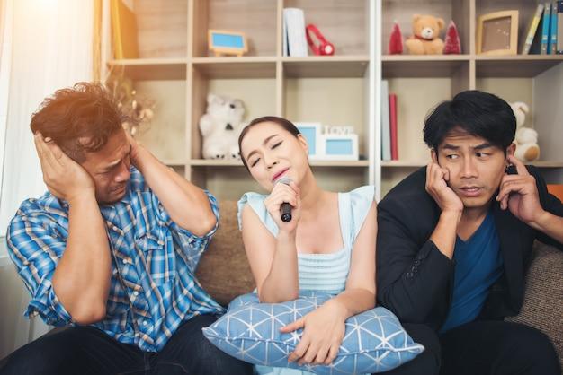 Grupo de amigos divirtiéndose en la sala de estar cantando una canción juntos