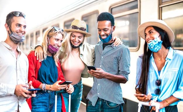 Grupo de amigos divirtiéndose con teléfonos móviles inteligentes mientras espera el tren en la estación de tren