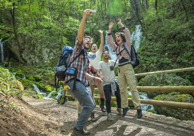 Grupo de amigos divirtiéndose y tomando selfies en la naturaleza.