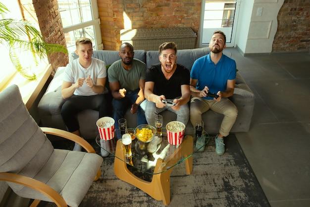 Grupo de amigos emocionados jugando videojuegos en casa.