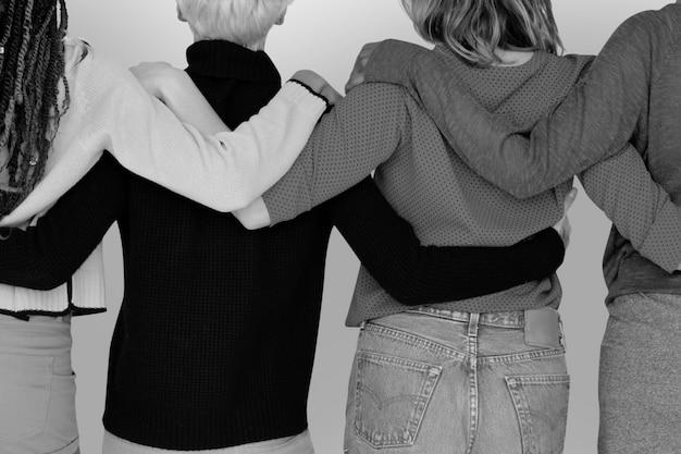 Grupo de amigos en escala de grises abrazándose unos a otros