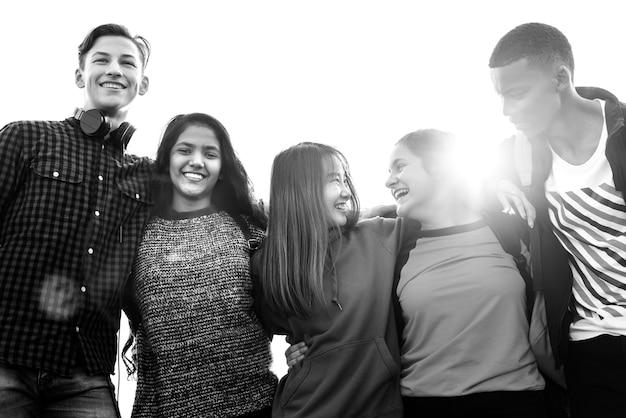 Grupo de amigos de la escuela al aire libre se arracima mutuamente unidad y concepto de comunidad