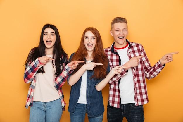 Grupo de amigos de la escuela alegre señalando con el dedo lejos