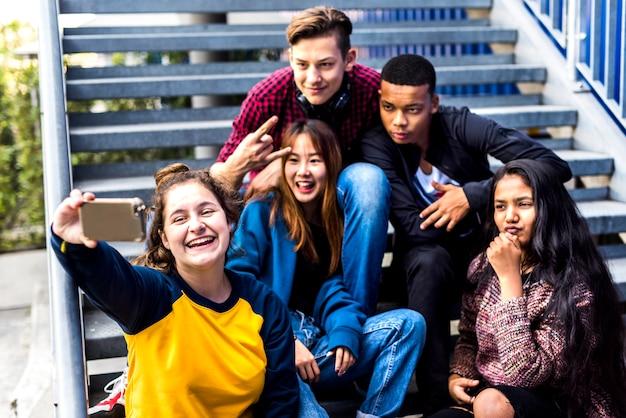 Grupo de amigos de la escuela divirtiéndose y tomando un selfie.