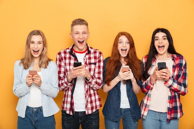 Grupo de amigos de la escuela emocionados con teléfonos móviles
