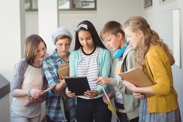 Grupo de amigos de la escuela mediante tableta digital en el pasillo