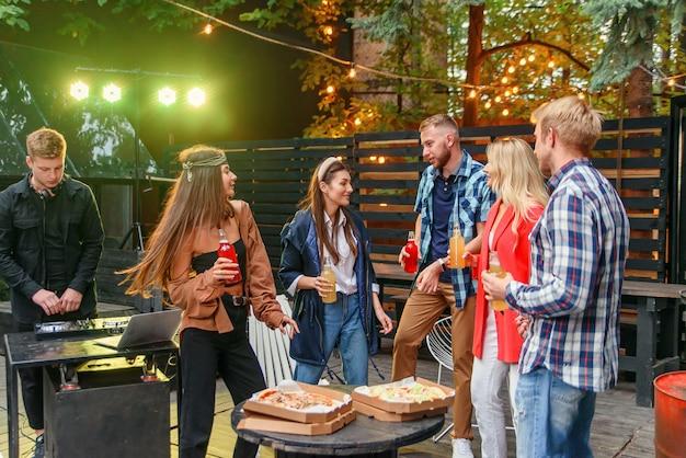 Grupo de amigos están bailando en la fiesta de barbacoa al aire libre en el patio de la casa.