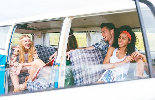 Grupo de amigos de estilo hippie que viajan juntos con una furgoneta vintage