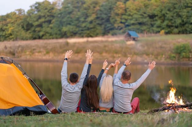Grupo de amigos felices acampando en la orilla del río, bailando levanta las manos y disfruta de la vista.