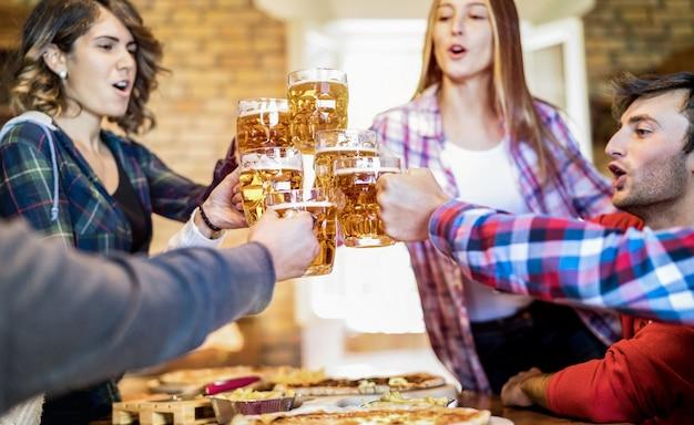 Grupo de amigos felices bebiendo cerveza y comiendo pizza en el bar restaurante
