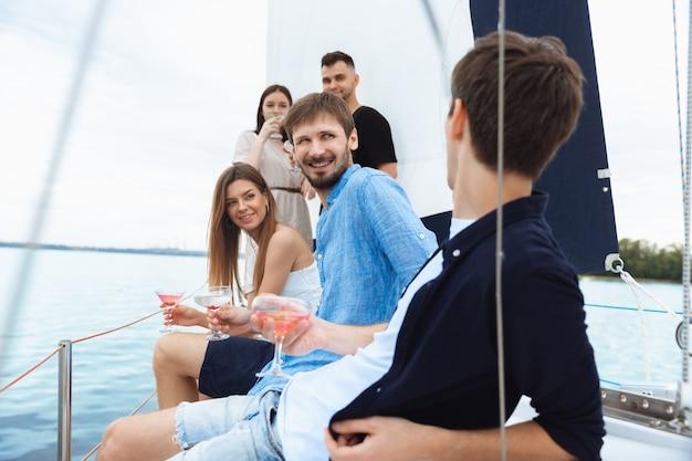 Grupo de amigos felices bebiendo cócteles de vodka en fiesta en barco al aire libre, verano