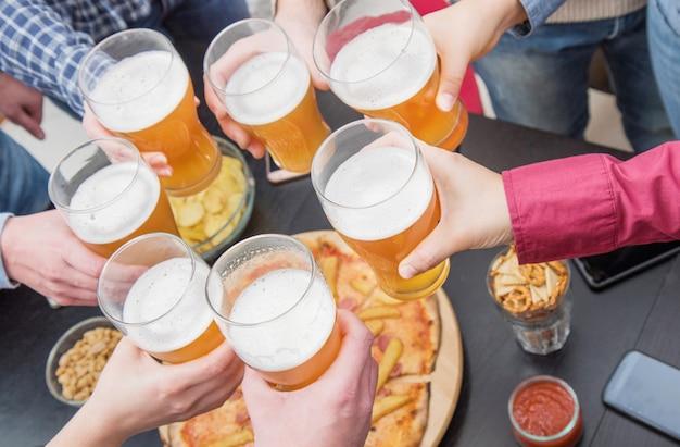 Grupo de amigos felices bebiendo y tostando cerveza en pub