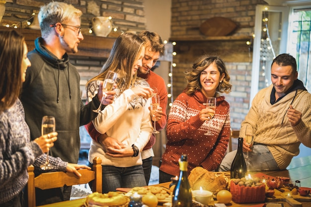 Grupo de amigos felices celebrando la fiesta de navidad con vino blanco y dulces en la cena.