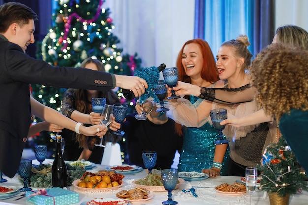 Grupo de amigos felices celebrando la navidad o el año nuevo. un hombre vierte champán en copas. las mujeres ríen, sentadas en una mesa cerca del árbol de navidad.