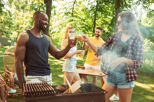Grupo de amigos felices con cerveza y fiesta de barbacoa en un día soleado. descansar juntos al aire libre en un claro del bosque o en el patio trasero. celebrar y relajarse, reír. estilo de vida de verano, concepto de amistad.