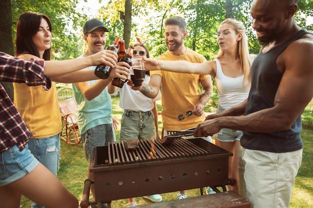Grupo de amigos felices con cerveza y fiesta de barbacoa en un día soleado. descansar juntos al aire libre en un claro del bosque o en el patio trasero