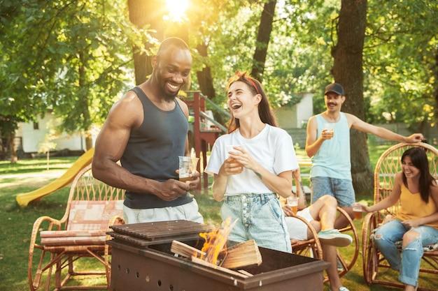 Grupo de amigos felices con cerveza y fiesta de barbacoa en un día soleado.