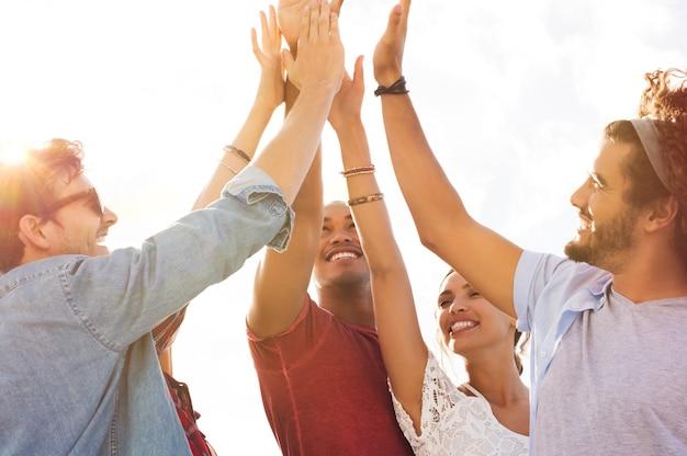 Grupo de amigos felices choca esos cinco y divirtiéndose juntos