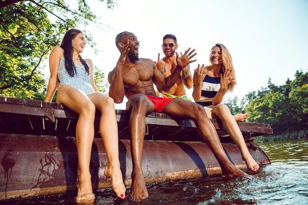 Grupo de amigos felices divirtiéndose mientras está sentado y riendo en el muelle en el río