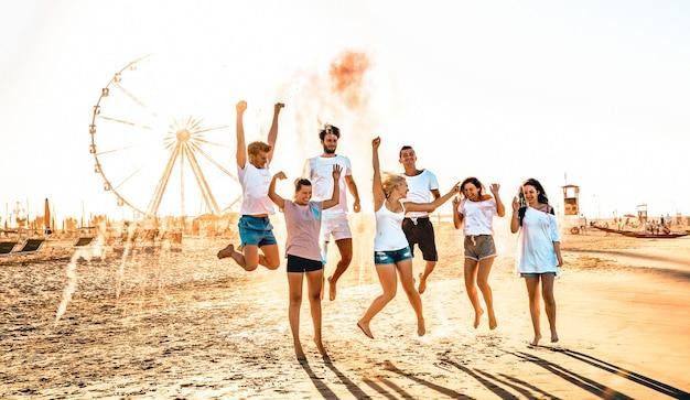 Grupo de amigos felices divirtiéndose en la noria junto al mar
