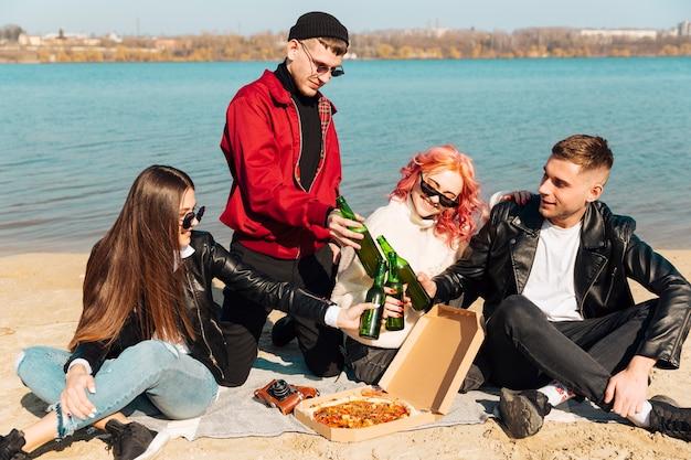 Grupo de amigos felices divirtiéndose y tintineando botellas en la playa