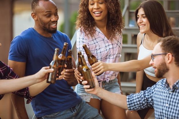 Grupo de amigos felices con fiesta de cerveza en día de verano. descansar juntos al aire libre, celebrar y relajarse, reír. estilo de vida de verano, concepto de amistad.