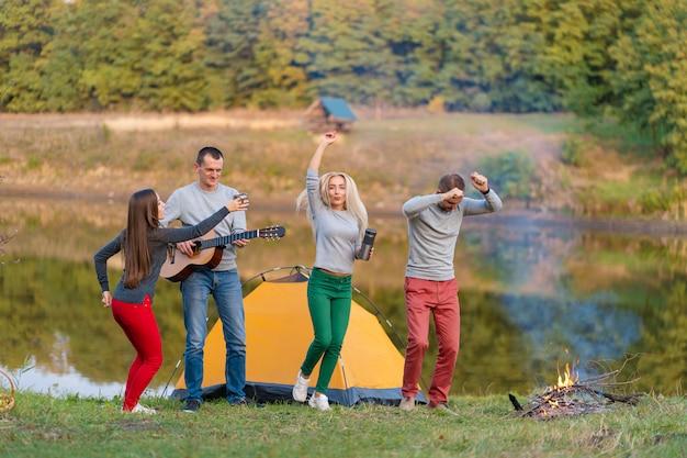 Grupo de amigos felices con guitarra, divertirse al aire libre, bailar y saltar cerca del lago en el fondo del parque el hermoso cielo. divertido camping