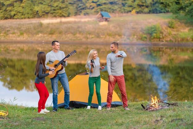 Grupo de amigos felices con guitarra, divertirse al aire libre, bailar y saltar cerca del lago en el parque