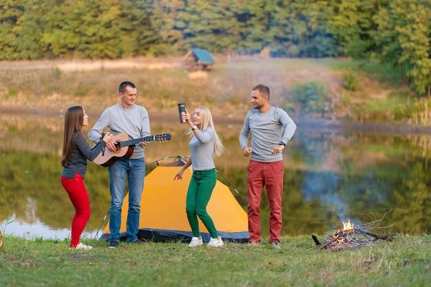 Grupo de amigos felices con guitarra, divirtiéndose al aire libre, bailando y saltando