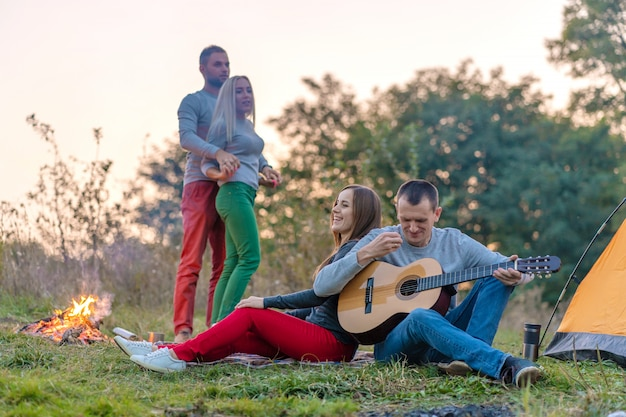 Grupo de amigos felices con guitarra, divirtiéndose al aire libre, cerca de fogatas y carpa turística, camping divertido familia feliz
