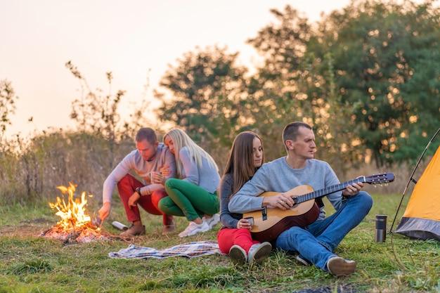 Grupo de amigos felices con guitarra, divirtiéndose al aire libre, cerca de la hoguera y tienda turística. camping divertido familia feliz