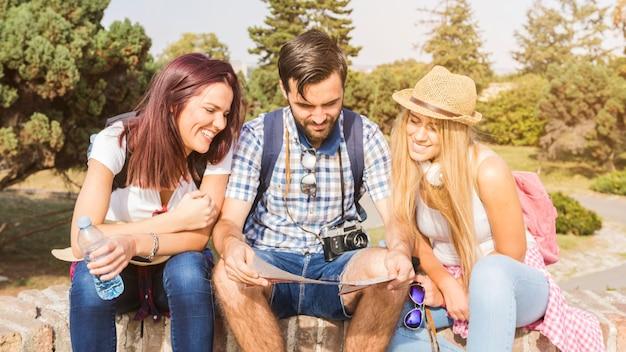 Grupo de amigos felices mirando el mapa