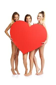 Grupo de amigos felices posando desnuda con corazón sobre fondo blanco.