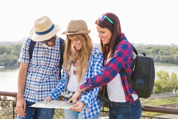 Grupo de amigos felices que buscan ubicación en el mapa.