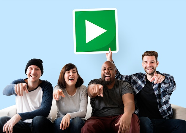 Grupo de amigos felices que sostienen un botón de reproducción