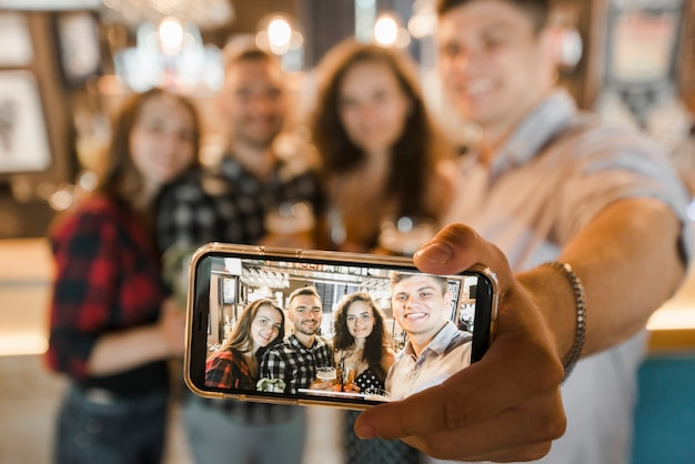 Grupo de amigos felices que toman selfie en teléfono móvil