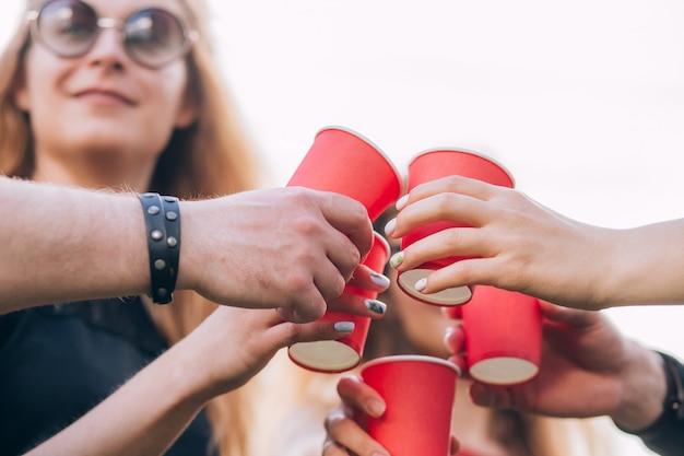 Grupo de amigos felices relajantes en la naturaleza con tazas rojas de alcohol.