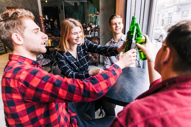 Grupo de amigos felices sentados alrededor de la mesa de madera tostando las botellas de cerveza verde en pub