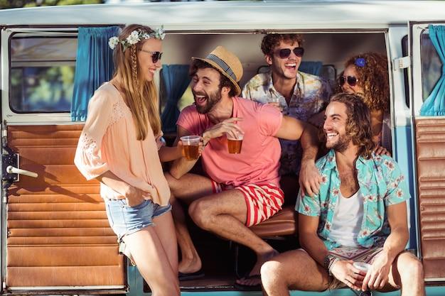Grupo de amigos felices sentados en autocaravana y bebiendo cerveza