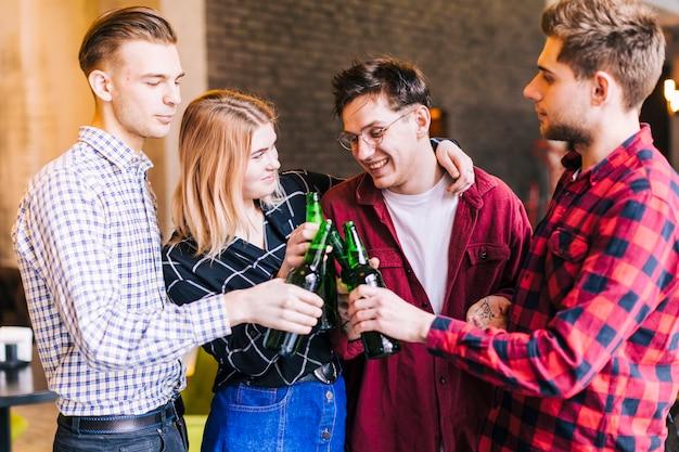 Grupo de amigos felices tintineando la botella de cerveza