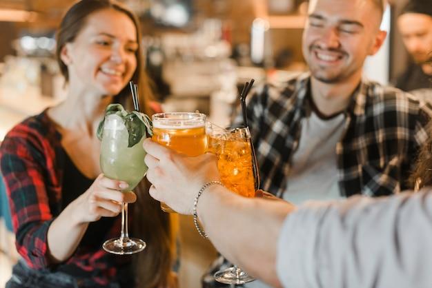 Grupo de amigos felices tostado bebidas mientras de fiesta en pub