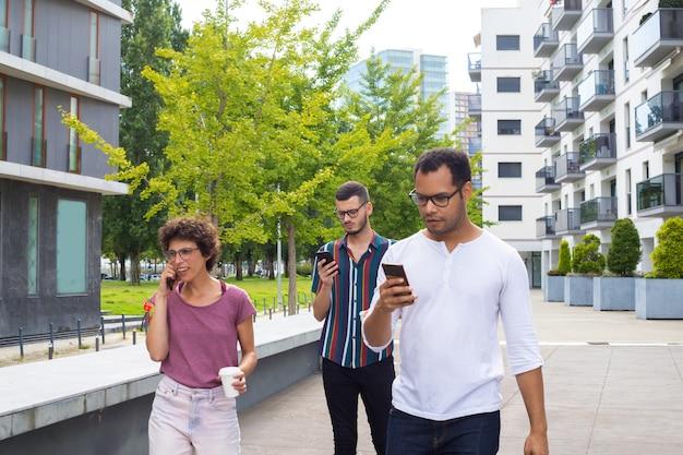Grupo de amigos con gadgets caminando afuera