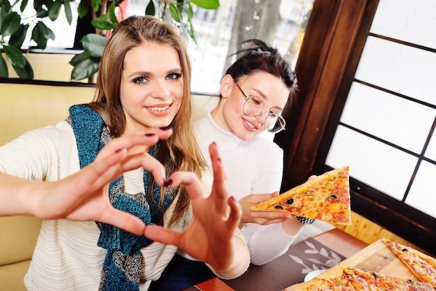 Un grupo de amigos habla y sonríe en un café y come pizza.