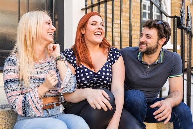 Grupo de amigos hablando y riendo juntos.